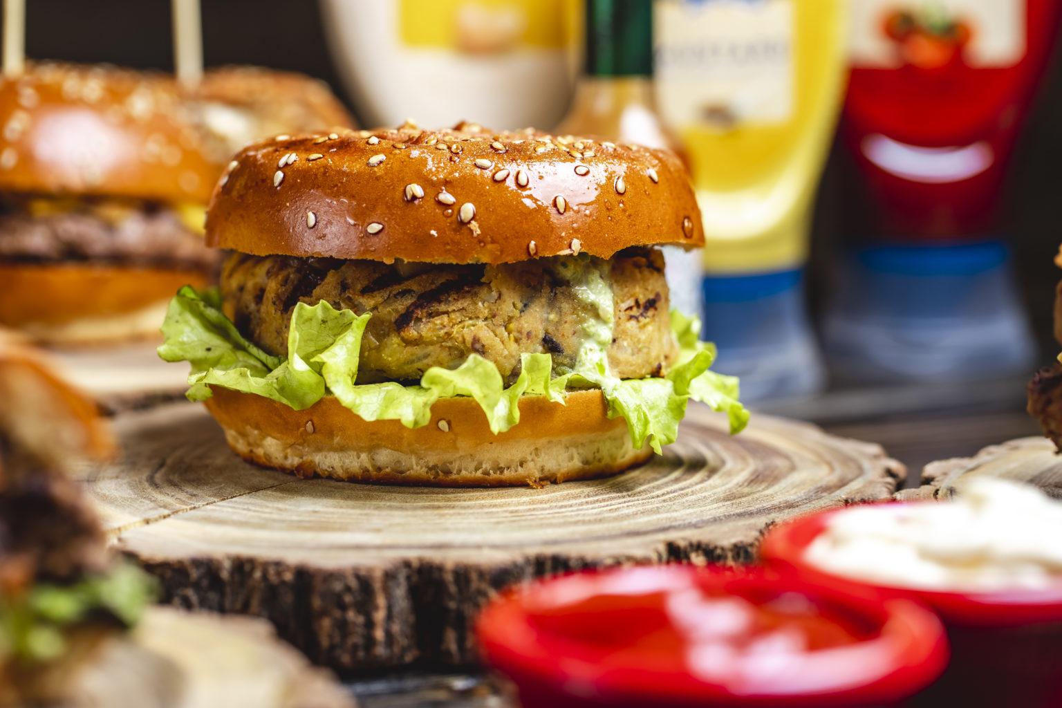 side view veggie burger vegetarian burger and lettuce leaf between burger buns
