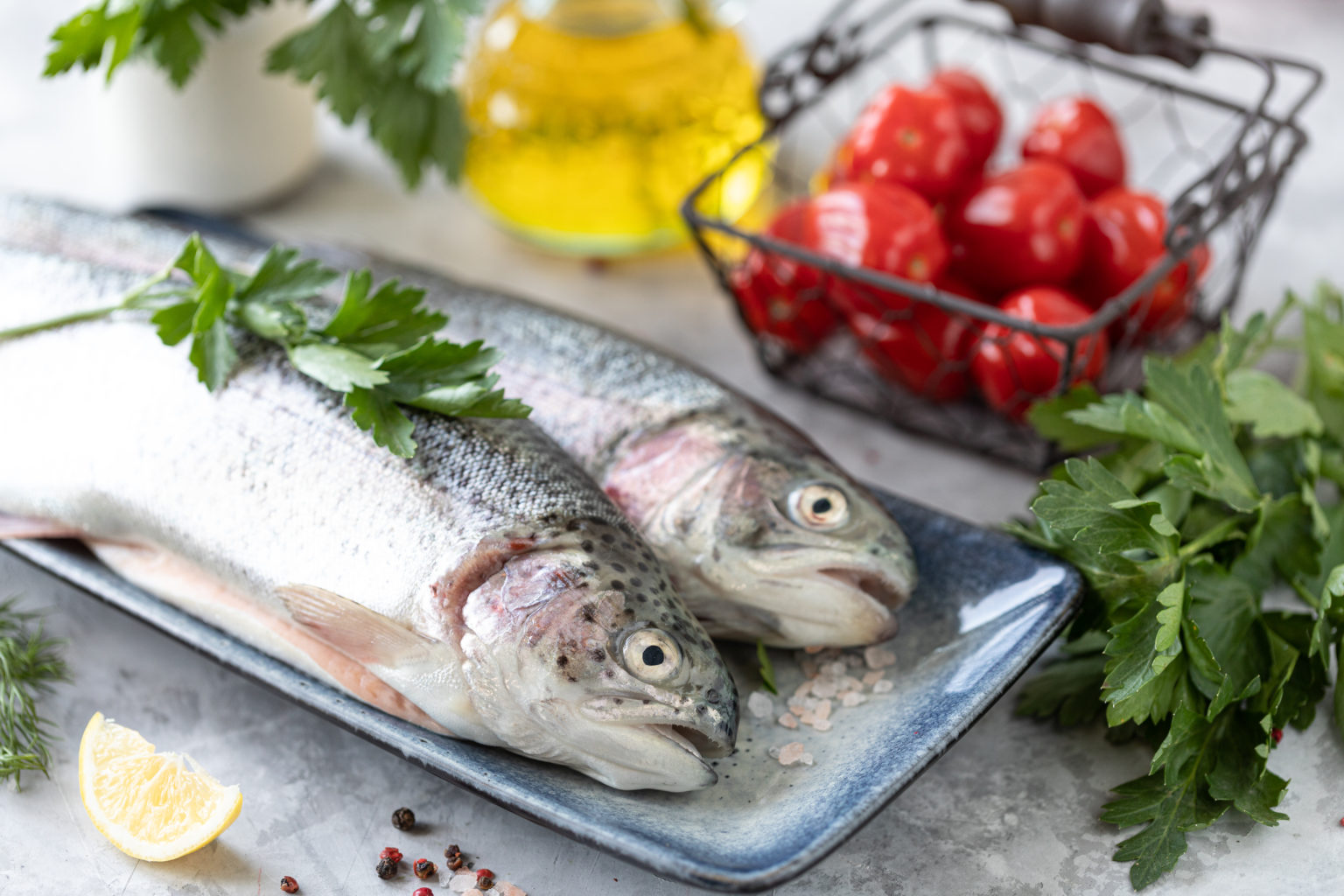 Two raw rainbow trout fish on a plate, greens and fresh vegetables for preparing healthy and tasty food. Healthy diet and delicious culinary concept. Copy space.