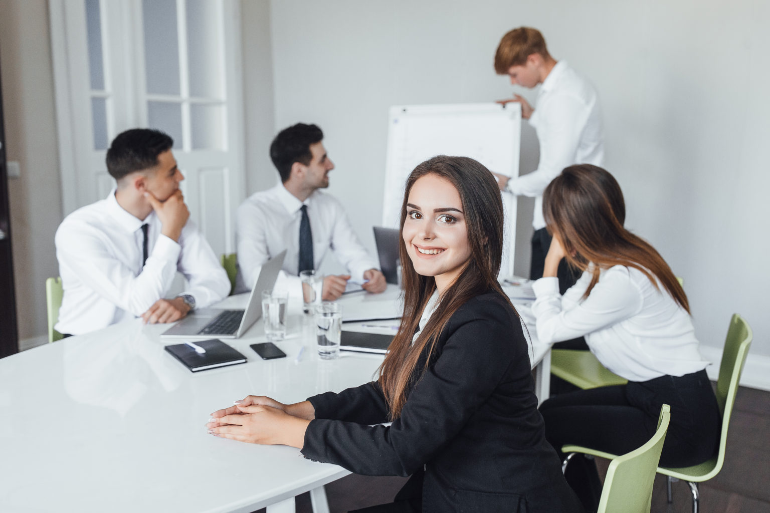 Young beautiful business lady in business wearing a business meeting with colleagues at work in a modern office.