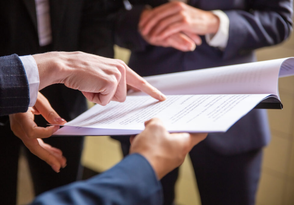 Cropped view of businesswomen reading document. Closeup shot of female finger pointing at page. Business concept
