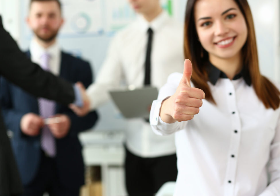 Woman showing confirm symbol during conference in office as high level and quality of product or mediation gratitude concept