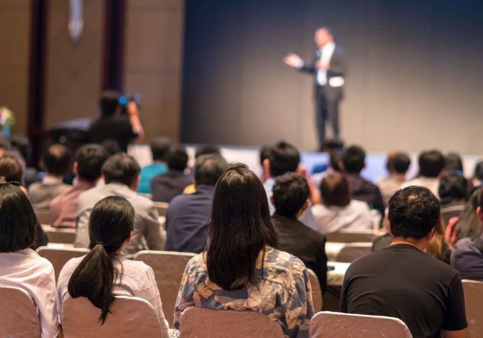 Rear side of Audiences sitting and listening the speackers on the stage in low light conference hall, event and seminar concept