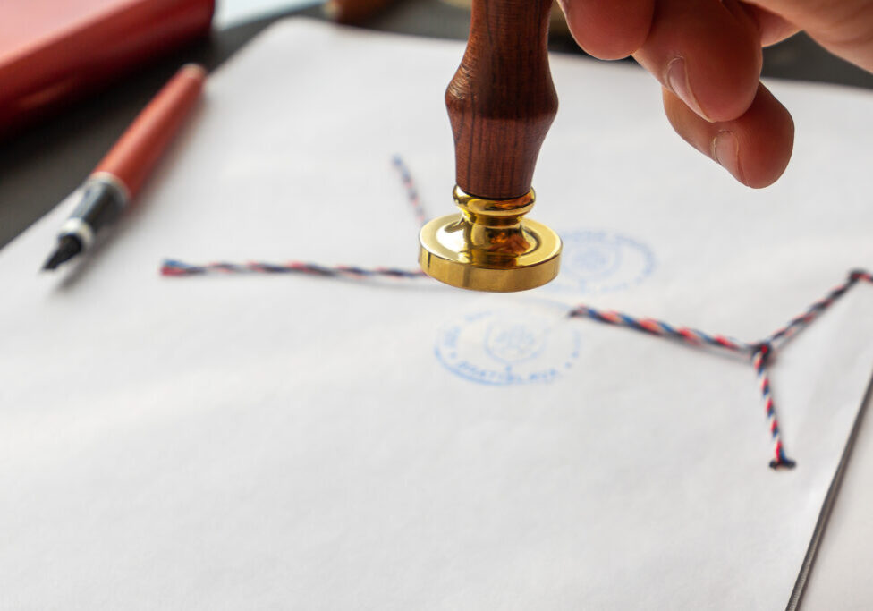 Notary public wax stamper. White envelope with brown wax seal, golden stamp. Responsive design mockup, flat lay. Still life with postal accessories