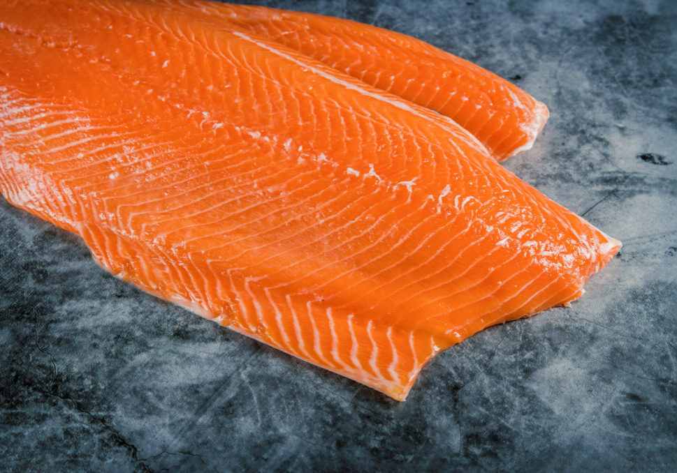 Delicious raw salmon fillet on dark background with space for text. food, health cooking Top view.
