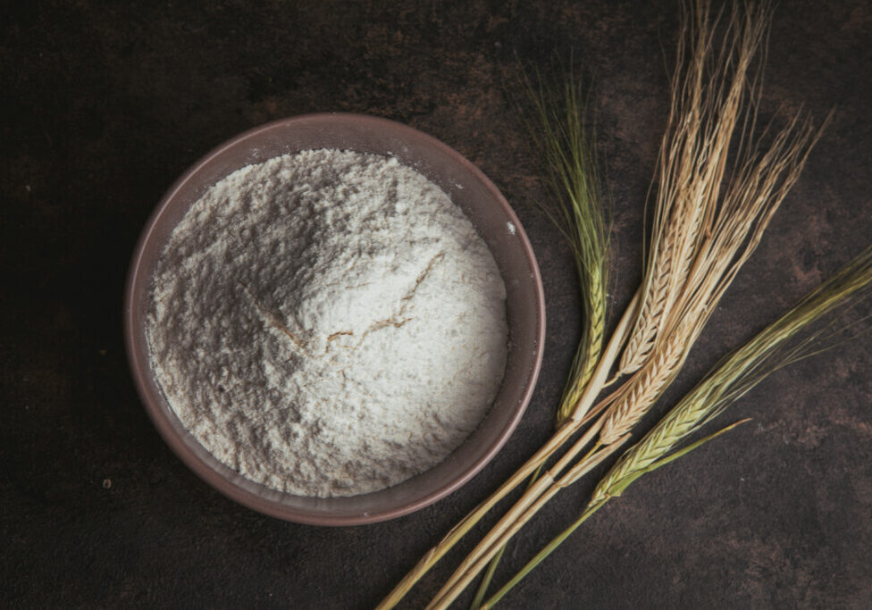 Flour in a bowl with wheat flat lay on a dark brown background