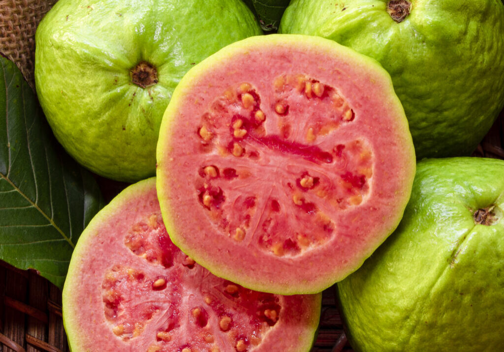 Closeup on red guava sliced with green leaf on rustic wooden background.