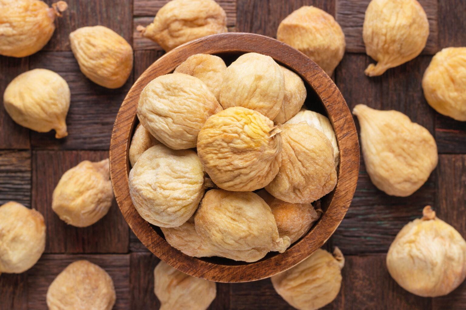 dried figs in bowl on wooden table background.